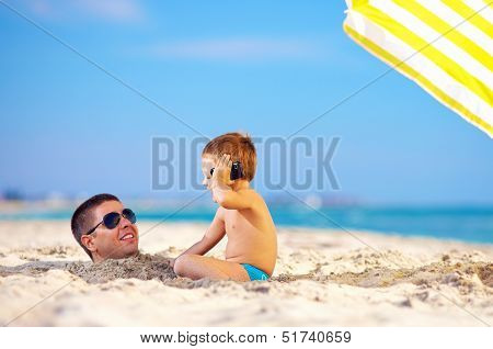 Happy Kid Talking On The Phone, Father Head In Sand