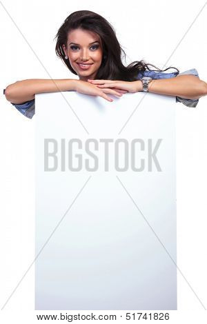 young casual woman smiling from behind a blank pannel. on white background