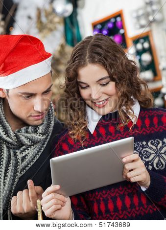 Young couple using digital tablet together at Christmas store