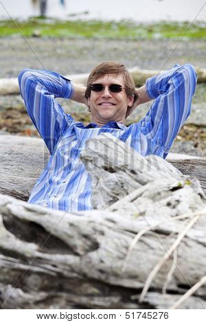 Man In Forties Leaning Back Against Log On Beach