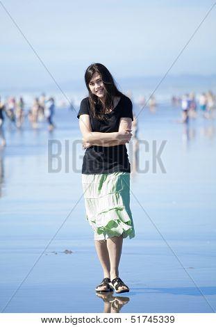 Beautiful Biracial Young Woman Or Teen Walking Along Beach By Pacific Ocean