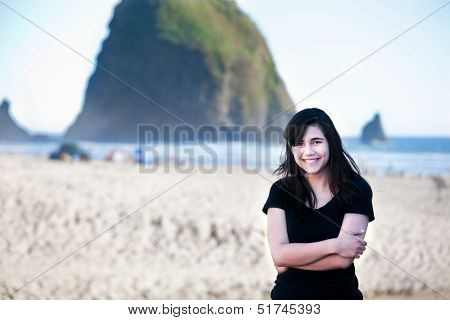 Smiling Biracial Young Woman Standing On Beach By Ocean