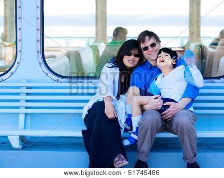 Interracial Couple Holding Disabled Son On Ferry Boat Deck