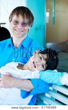 Handsome Father In Forties Holding Disabled Son In Arms