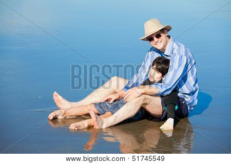 Father Playing With Disabled Son On Beach, Holding Him Upright