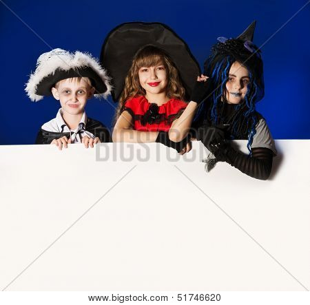 Happy children in halloween costumes posing over dark background. Copy space.