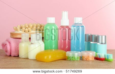 Hotel amenities kit on table on pink background