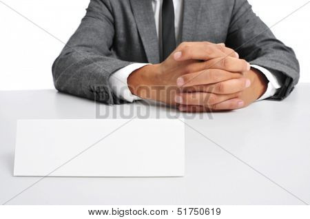 a man wearing a suit sitting in a desk with a blank signboard in front of him with a copy-space