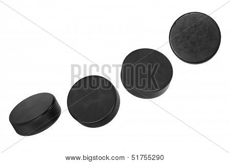 Four Hockey Pucks