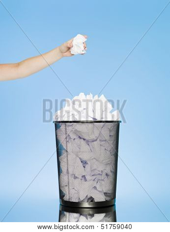 Hand trowing a paper into a wastebasket on blue background