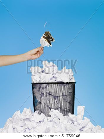 Hand holding a piece of paper in flames over a wastebasket