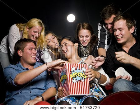 Group of young spectators eating popcorn at the movie theater