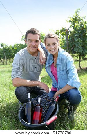 Couple in vineyard presenting wine production