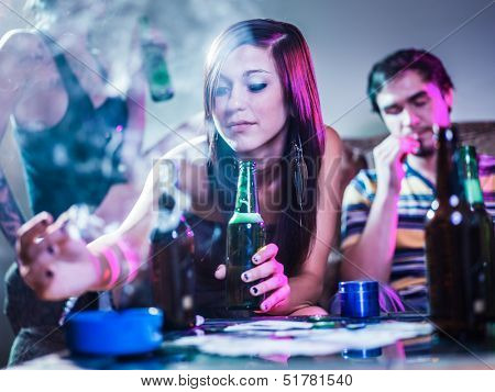 girl putting joint in ashtray at crazy party