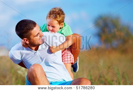 Father And Son Having Fun Playing At Summer Field