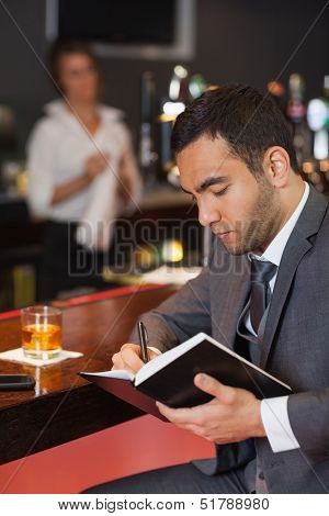 Cheerful businessman writing on his datebook in a classy bar