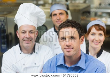 Young manager posing in a kitchen with chefs smiling at camera