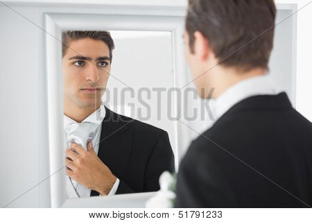 Serious handsome bridegroom looking in mirror straightening his tie