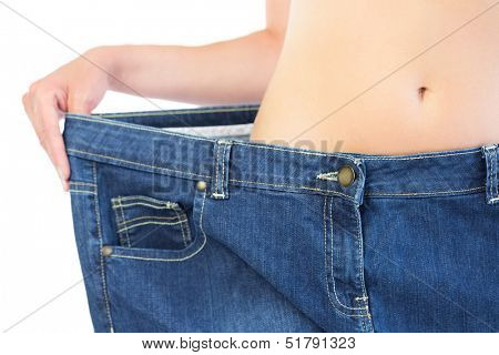 Extreme close up of confident slender blonde wearing too big trousers on white background