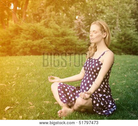 Beautiful pregnant woman relax in meditation in park, yoga for pregnant, toned