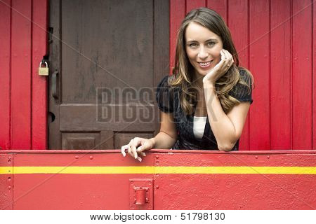 Portrait of happy young woman leaning on railing in red train caboose car