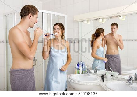 Young Couple looks at eachother affectionately, whilst Brushing their Teeth In the Bathroom