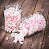 Pink and white marshmallows spilling from a storage jar, over old wood background. Vintage effect wi