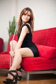 stock photo of sado-masochism  - young beautiful woman sitting on a red couch and holding a steel chain - JPG