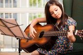 pic of guitar  - Pretty little girl practicing some new sound on a guitar at home - JPG
