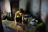 Woman make girdle cake (banh trang)