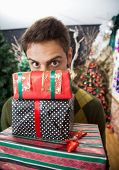 Portrait of young man with raised eyebrows looking over stacked Christmas gifts in store