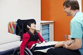 picture of biracial  - Disabled boy in wheelchair sharing laugh with his doctor or therapist - JPG