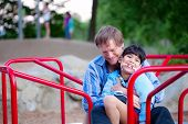 stock photo of babysitter  - Father playing with disabled son on merry go round at playground - JPG