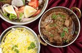 Indian copper dishes with homemade beef rogan josh, white and yellow rice and a salad, seen from abo