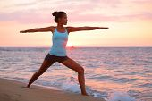 stock photo of serenity  - Yoga woman in zen meditating in warrior pose relaxing outside by beach at sunrise or sunset - JPG