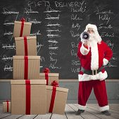 stock photo of baby delivery  - Santa Claus with megaphone with list of gifts delivery in a blackboard - JPG