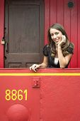 Portrait of beautiful young woman leaning on railing in red train caboose car