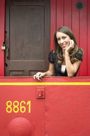 stock photo of caboose  - Portrait of beautiful young woman leaning on railing in red train caboose car - JPG