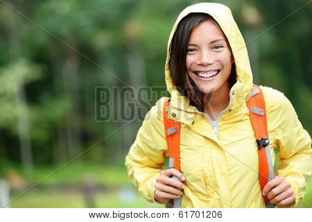 Rain woman hiking happy in forest. Female hiker portrait standing with backpack joyful on rainy day wearing yellow raincoat outside in nature forest by. Multi-ethnic Asian girl.