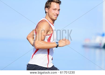 Running man runner looking at camera smiling funny flirtatious or playful. Handsome good looking male fitness model jogging outside on beach training living healthy lifestyle. Young guy in his 20s.