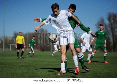 KAPOSVAR, HUNGARY - MARCH 1: Unidentified players in action at the Hungarian National Championship U17 game between Kaposvar (white) vs Ferencvaros (green) March 1, 2014 in Kaposvar, Hungary.