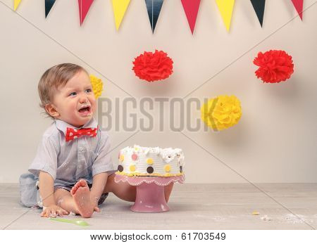Baby boy crying while eating his birthday party cake. Smash the cake party
