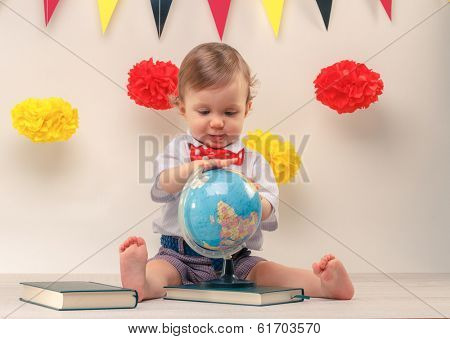 Adorable smiling curious baby boy studying an earth globe. Education concept.