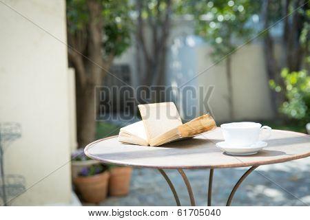 Vintage books and coffee cup on table