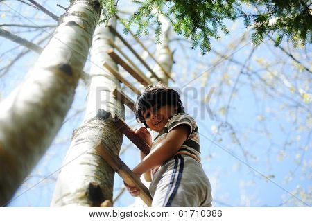 Happy kid having fun climbing on ladder in forest cabin