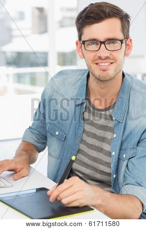 Casual male photo editor using graphics tablet in a bright office