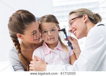 Mother with girl being examined by female doctor with otoscope in clinic