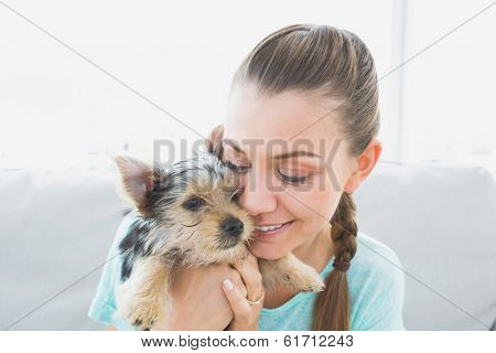 Smiling woman cuddling her yorkshire terrier puppy at home in the living room