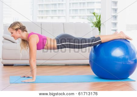 Slim blonde in plank position using exercise ball at home in the living room