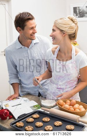 Portrait of a happy young couple preparing cookies in the kitchen at home